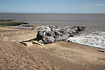 Rock armour reinforcing old concrete groyne on beach. Coastal defences, Felixstowe, Suffolk, England
