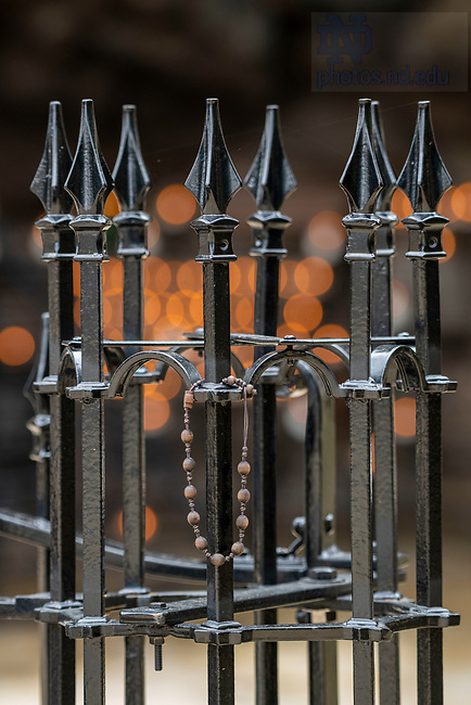 March 27, 2020; A bracelet hangs on the wrought iron fence at the Grotto.  (Photo by Barbara Johnston/University of Notre Dame)