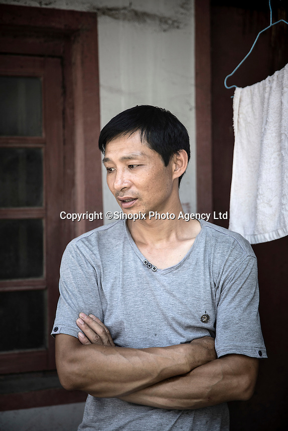 Restaurant owner and former truck driver Dong Haiqiang at his small restaurant in Xingxing village on the outskirts of Shanghai,  China on 14 August 2015.  As China's sputtering economy has beginning to affect employment, many migrants who used to live in the village to work on Shanghai's numerous construction sites and factories are beginning to thin out.