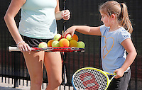 NWA Democrat-Gazette/DAVID GOTTSCHALK  Erica Rogers (left), with the Arkansas Tennis Association (cq), collects tennis balls Thursday, September 10, 2015 with Katherine Skinner, a second grade student at Vandergriff Elementary School, as they participate in a Free Play Day tennis clinic on the courts at the elementary school in Fayetteville. A joint use agreement grant between the U.S. Tennis Association and Vandergriff Elementary School has allowed the school to open the courts to the public after school hours on weekdays beginning at 4:00 p.m. and all day on the weekends.