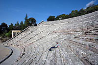 EPIDAURUS, GREECE - APRIL 14 : A low angle view of the Cavea of the Theatre, on April 14, 2007 in Epidaurus, Greece. The Theatre, designed by Polykleitos the Younger, was built in the late 4th century BC and extended in the Hellenistic period. It was rediscovered in 1881 and significantly restored in the 1950s.  It has the three main features of a Greek theatre: the orchestra, a sunken round stage; the skene, a raised rectangular stage beyond the orchestra; and the cavea, a raked semi-circular auditorium, in which a woman is sitting, divided by radiating diazomas. Between the cavea and orchestra may be seen a paved depression for drainage. The theatre is renowned for its accoustics thanks to the symmetry of the cavea, seen here in the afternoon light. (Photo by Manuel Cohen)