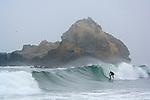 Man surfing on breaking waves next to coastal rock in fog, Pfeiffer Beach, Big Sur Coast, Monterey County, California
