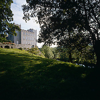 A glimpse of the front facade of Kiltinan Castle from the wooded valley below the property