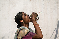 8 months pregnant, 21 year old Jhansi Aitharam drinks iJal water in the courtyard of her house in Ambedkar Nagar, Medak, Telangana, India.