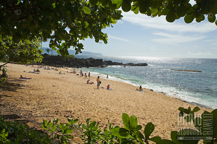 People enjoying Three Tables Beach near Pupukea, on Oahu's North Shore, seen through the trees