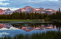 Early morning reflection of mountain peaks at Red Rock Lake, located in the Front Range near the town of Ward, Colorado