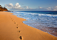 Sunrise at Secret Beach with footprints in the sand, Kauai, Hawaii.