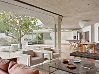 The contemporary home has a relaxed, peaceful quality with a seamless connection between indoor and outdoor living. The main floor is a large space without walls that connects the dining room, the living room, the bar, the kitchen and the pool on the right side. Concrete is used in the ceilings and walnut wood floors add warmth.