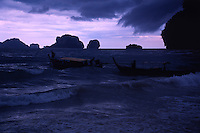 Thai fisherman launch their flimsy vessels in a strange seascape of jutting limestone pillars and jungle - backed empty beaches. Mueang Krabi District Southern Thailand.