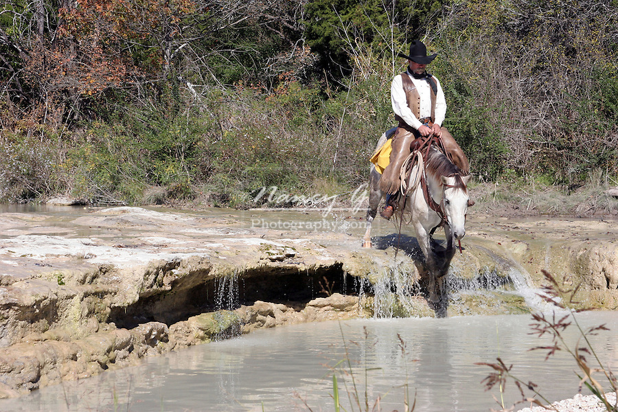 A cowboy and horse crossing a stream in Texas