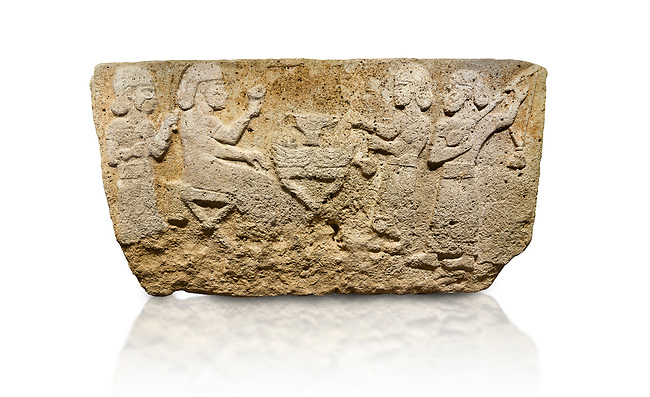 Hittite monumental relief sculpted orthostat stone panel from Water Gate Limestone, Karkamıs, (Kargamıs), Carchemish (Karkemish), 900-700 BC.  Anatolian Civilisations Museum, Ankara, Turkey.<br /> <br /> The figure sitting on a stool to the left of the table holds a goblet in his right hand which he raised upwards. Behind, there is a servant with a fan in his hand. On the other side of the table is another servant waits with a vessel in the hands. The rightmost figure plays a Saz (a stringed musical instrument) with the tassel on the handle. <br /> <br /> On a white background.