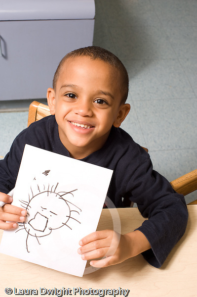 Preschool ages 3-5 proud boy holding up drawing smiling vertical