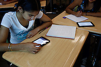 "Lindsay, California, September 5, 2012 - Jasdeep Bains uses a Kindle to do course work in Adrian Gutierrez's Spanish I class. Principal Jaime Robles says that the school used to ban phones and and tablets, but now they embrace them. This is how students communicate and learn. So we are using the tools that they use to keep them engaged.""..Lindsay High School began building a competency-based education model about 7 years ago, fully implementing it just over three years ago and is set to graduate its first class this school year. This model does away with traditional grading and pass/fail for grades. Instead students are expected to achieve proficiency in a range of areas in each class, where a 3 (equal to a traditional B) is passing; A 4 is considered intensive and usually denotes college bound. Says Principal Jaime Robles, ?This allows students to learn at there own pace. If a student is advanced, they can move ahead, and if a student is lagging, they get the support they need.? Part of this model allows for students who are more advanced dig deeper and push harder and truly move ahead of others. Because they are ahead, some spend the extra time learning more, others take concurrent classes at the nearby community college and some choose to graduate early to start their path. ?Each student has their own set of goals,? says English teacher Amalia Lopez, ?Whatever their goals are, we support them.?.Slug: DD_ CompetencyByline: Daryl Peveto / LUCEO for Education Week"