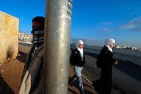 ABU DIS / GERUSALEMME / ISRAELE.GIOVANI PALESTINESI BLOCCATI NELLA NOTTE DALLA POLIZIA ISRAELIANA AL CHECKPOINT DI ABU DIS ALLE PORTE DI GERUSALEMME CERCANO DI SCALDARSI BRUCIANDO PEZZI DI CARTONE..DA QUANDO E' STATO COSTRUITO IL MURO, PER LA POPOLAZIONE PALESTINESE CI SONO SEMPRE PIU' LIMITAZIONI ALLA LIBERTA' DI MOVIMENTO. DISTRUZIONE DELLE CASE PALESTINESI E CONFISCA DELLE TERRE A RIDOSSO DEL MURO SONO DIVENTATE PRATICA COMUNE IN NOME DELLA SICUREZZA DI ISRAELE..FOTO LIVIO SENIGALLIESI..ABU DIS / JERUSALEM / ISRAEL.YOUNG PALESTINIANS STOPPED BY ISRAELI SECURITY FORCES AT THE CHECKPOINT. THE SITUATION FOR PALESTINIAN PEOPLE IS VERY BAD AND THERE IS NOT FREEDOM OF MOVEMENT.  EVERY DAY SOLDIERS AND JEW SETTLERS MAKE VIOLATIONS OF HUMAN RIGHTS AND CONFISCATION OF PALESTINIAN LANDS AND HOUSES..PHOTO LIVIO SENIGALLIESI