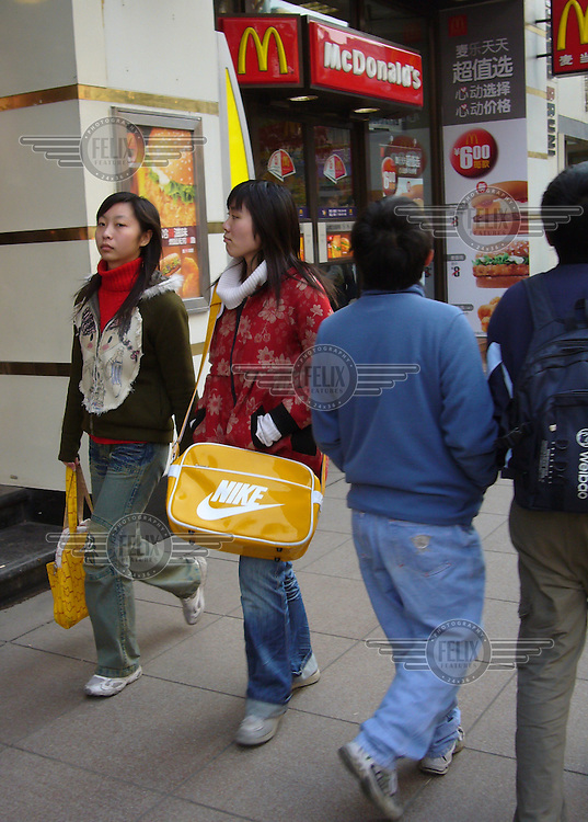 A young woman with a Nike bag walks past a McDonald's restaurant in Shanghai.