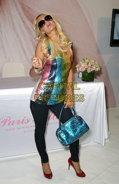 PARIS HILTON.Launches her sunglasses collection with Gripping Eyewear Inc. at Vision Expo West at the Sands Expo Center inside the Venetian Resort Hotel and Casino, Las Vegas, Nevada, USA, .2nd October 2009..full length  white top t-shirt blue bag jeans snake print red yellow green rainbow multi-coloured striped sunglasses pink frames skinny red shoes patent heels jeggings sequined sequin sleeveless .CAP/ADM/MJT.©MJT/Admedia/Capital Pictures
