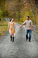 Young couple holding hands walking on country road