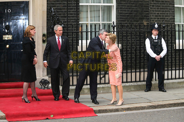 SARAH BROWN, PRESIDENT GEORGE W. BUSH, GORDON BROWN PM & FIRST LADY LAURA BUSH.President Bush and his wife Laura visit the Prime Minister Gordon Brown and his wife Sarah Brown for an informal dinner on Bush's farewell tour, 10 Downing Street, London, England, .15th June 2008.full length red carpet outside policeman photocall posing black suit peach skirt jacket greeting kissing hugging embracing.CAP/DS.©Dudley Smith/Capital Pictures