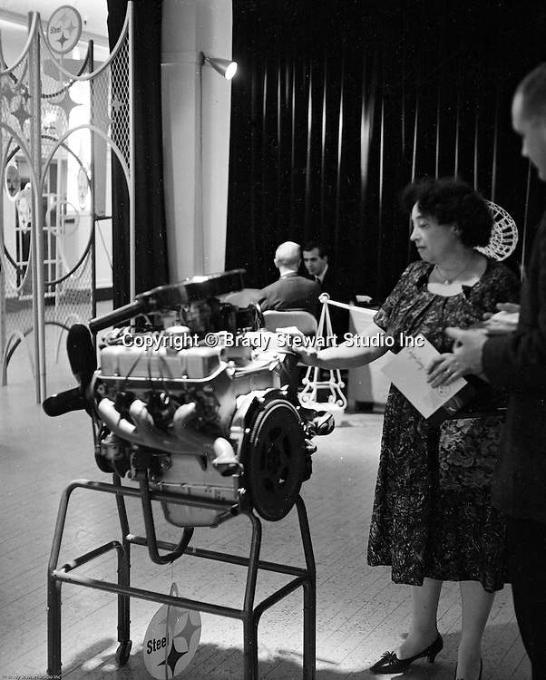 Pittsburgh PA: View of a woman looking at a US Steel engine block display at Horne's department store in downtown Pittsburgh. The engine block display was part of US Steel's display at Horne's during the Rhapsody of Steel campaign.  US Steel launched an awareness campaign of all the current uses of steel in everyday products.  During this time, ALCOA Aluminum Company of America also headquartered in Pittsburgh, was aggressively competing to enter markets where US  steel companies traditional dominated market share. Examples included beer and food Cans, appliances, automobile parts, children toys / bicycles, and more.