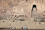 November 2012, Bamiyan, Afghanistan: Local people cross a field in front of the empty Buddhas of Bamiyan niches, two 6th century monumental statues of standing buddha carved into the side of a cliff in the Bamyan valley in the Hazarajat region of central Afghanistan.The valley is home to many Hazara's, who have often made up vast numbers of refugees to Australia, having been persecuted and driven from their homes in both Afghanistan as well as from Quetta in Pakistan where a lot of displaced Hazara fled to during the Taliban years. Bamiyan is home to a lot of Hazara who are Shia muslim and as such are looked down upon by the Sunni Pashto tribes that make up the population majority in Afghanistan.   Picture by Graham Crouch/The Australian Magazine.