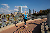 A female running on the Lamar Street Pedestrian Bridge with a blue sky day with dramatic clouds and Austin Skyline.