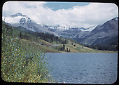 View from near the Trout Lake dam showing the water tank and an approaching northbound RGS freight train in the distance.<br /> RGS  Trout Lake, CO  ca. 1950