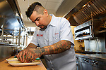 STAMFORD, CT - JULY 17, 2014: Chef Aaron Sanchez plates a dish in the kitchen at Paloma. CREDIT: Clay Williams for Paloma.<br /> <br /> <br /> &copy; Clay Williams / http://claywilliamsphoto.com
