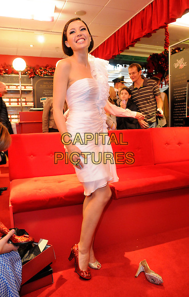 DANNII MINOGUE.Dannii Minogue turns on the Emerald City Lights at Harrods, Knightsbridge, London, England, October 29th 2009..christmas xmas full length gold red trying on shoes glittery sparkly bows peep toe shoe.CAP/FIN.©Steve Finn/Capital Pictures.