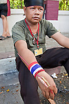 14 MAY 2010 - BANGKOK, THAILAND: A Red Shirt protester with rockets on his wrist at the intersection of Rama IV and Witthayu Roads in Bangkok Friday morning. Tensions among Red Shirt protesters demanding the dissolution of the current Thai government rose overnight after Seh Daeng, the Red Shirt's unofficial military leader was shot in the head by a sniper. Gangs of Red Shirts have taken over military checkpoints on Rama IV and are firing small rockets at military helicopters and army patrols in the area. Troops have responded by firing towards posters.  PHOTO BY JACK KURTZ