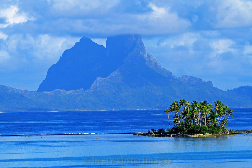 A small motu (atoll island) adorns the brooding peak of Bora Bora.