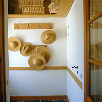 A collection of straw hats hangs from a simple set of hooks in this entrance hall with picnic baskets stored in readiness on open shelves above