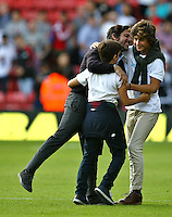 Quique Flores manager of Watford celebrates with his family (possibly) after the final whistle   during the Barclays Premier League match Watford and Swansea   played at Vicarage Road Stadium , Watford