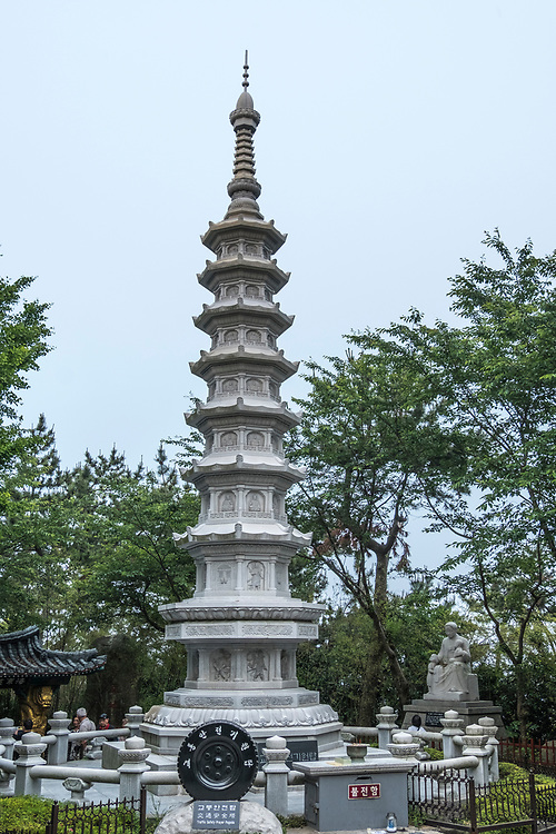 Leading to the temple complex, a towering seven-story stone pagoda that is intricately detailed in its design, is along the pathway. At its base is a tire shrine for people to pray to to avoid car accidents (seriously!).