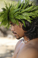 Male (kane) hula dancer deep in thought, wearing palapalai fern head lei, headshot.