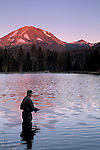 Person fishing near shore wading at Manzanita Lake below Mount Lassen at sunset, Lassen Volcanic National Park, California
