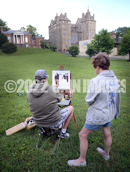 """Addie Hocynec, right, of Lansdale, Pennsylvania and a painter herself, speaks with fellow artist John Schmidtberger, left, as he paints a picture during the first ever Bucks County Plein Air Festival Wednesday June 8, 2016 at the Mercer Museum in Doylestown, Pennsylvania.  The competitively-selected artists will paint outdoors """"en plein air"""" or """"in open air"""" over the course of three days in various locations throughout the county to create various landscapes and streetscapes. (Photo by William Thomas Cain)"""