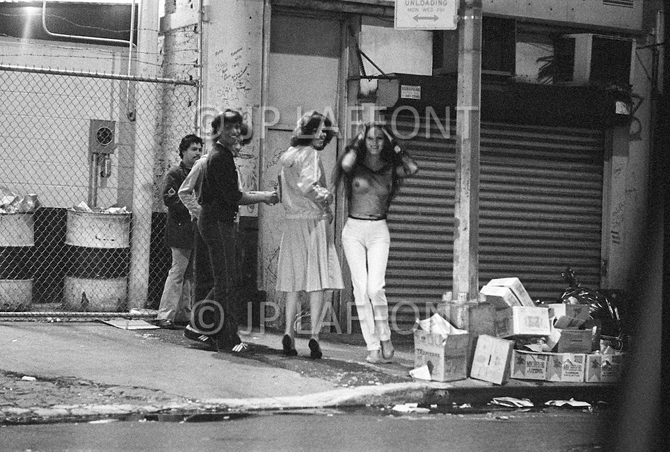 May, 1980. Manhattan, New York City, NY. Prostitution, drugs and pornography are everywhere in the streets. A transvestite prostitute displays his wares on a Times Square street. By 1980 Times Square had become a beehive of prostitution activity. And dealers are in each doorway.<br /> <br /> Manhattan, New York City, NY, Mai, 1980. La prostitution, la drogue, la pornographie et les fous rendent le quartier tr&egrave;s dangereux.<br /> 3 heures du matin : Times Square et les rues avoisinantes sont maintenant la proie de la prostitution agressive des homosexuels et des travestis et des vendeurs de drogues se placent dans chaque recoin obscure.