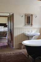 A bathroom leads off the master bedroom and is fitted with a free-standing antique clawfoot bath and painted tongue-and-groove panelling