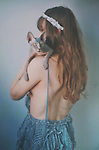 Young woman with bare back holding a cat