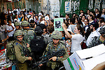 Israeli troops guard Israeli settlers during their weekly tour through the Old City of West Bank city of Hebron, 04 June 2016. Every Saturday a tour through Hebron's Old City, which is usually off limits for Israeli settlers, is organized by Israeli settlers and guests in Hebron. Palestians oppose those tours during which a guide explains about the alleged 'Jewish history' of the city also claiming that the Old City of Hebron is a Jewish property. Photo by Wesam  AL HASHLAMOUN.