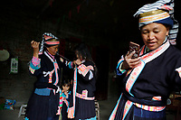 A woman of the ethnic Bouyei Tribe helps her daughter put on a traditional costume at home at Wangmo County in China's southwestern Guizhou Province, April 2019.