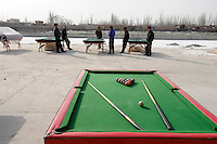 CHINA province Xinjiang city Kashgar where uyghur people are living , uighur men play pool outdoor in winter time / CHINA Provinz Xinjiang , Stadt Kashgar hier lebt das muslimische Turkvolk der Uiguren die durch massive Zuwanderung von Han Chinesen zur Minderheit werden , Uiguren spielen draussen Billiard im Winter