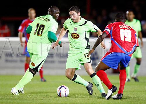 18.09.2012. Dagenham, ENGLAND: ..Ben Tozer of Northampton Town and Adebayo Akinfenwa of Northampton Town in action during the English League Two match between Dagenham & Redbridge and Northampton Town at The L.B Barking & Dagenham Stadium, London