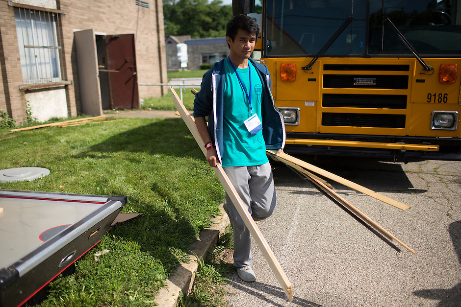 "Adam Madamba moves wood to a dumpster during ""Circle the City with Service,"" the Kiwanis Circle K International's 2015 Large Scale Service Project, on Wednesday, June 24, 2015, at the Friendship Westside Center for Excellence in Indianapolis. (Photo by James Brosher)"
