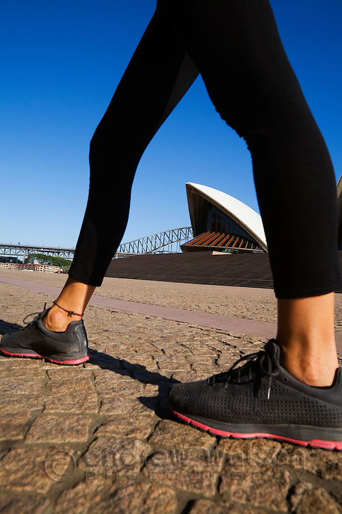 The Sydney Opera House is framed by the legs of a runner.  Sydney, New South Wales, AUSTRALIA.