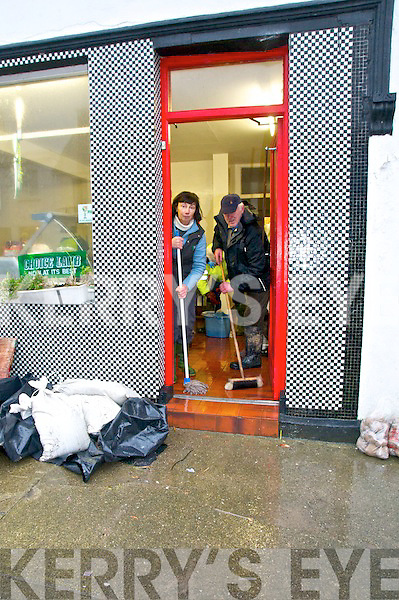 Flooding in Bridge St. Ballylongford. Mary & Tom Kelly sweeping ot the water from their Butcher's Shop.