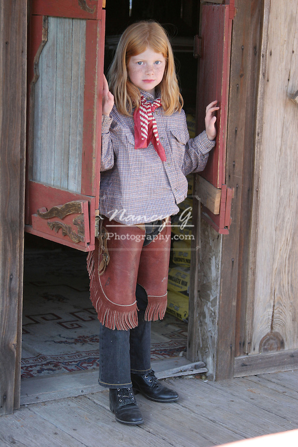 A young cowgirl walking out of a saloon bar in an old west town