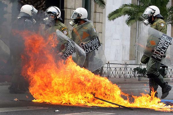 STC01 ATENAS (GRECIA) 23/02/2011.- Policía antidisturbios junto a las llamas de una bomba incendiaria que fue lanzada durante los enfrentamientos entre grupos de radicales y las fuerzas de orden ocurridos en la manifestación convocada con motivo de la huelga general contra la rígida política de ahorro del Gobierno, en el centro de Atenas (Grecia), hoy, miércoles, 23 de febrero de 2011. Los enfrentamientos tuvieron como escenarios principales las cercanías del Parlamento y del rectorado de la Universidad, donde los agentes emplearon gases lacrimógenos para dispersar a los manifestantes. Durante los enfrentamientos, un policía resultó herido cuando una bomba prendió fuego a su ropa, según informaron los medios locales. EFE/SIMELA PANTZARTZI