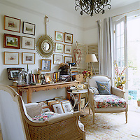 A collection of small framed prints and paintings displayed on a wall above a long wooden console table in the living room
