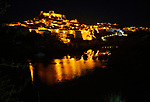 Historic hilltop walled medieval village of Mértola with castle, on the banks of the river Rio Guadiana, Baixo Alentejo, Portugal, Southern Europe nighttime with illumination of orange street lights